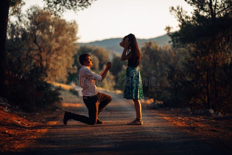 Man förälskat föreslå en förvånad chockad kvinna för att att gifta sig honom på solnedgången Förslag-, kopplings- och bröllopbegr royaltyfria foton