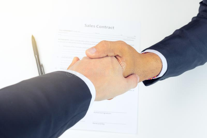 Man för affär som två till varandra skakar händer ovanför undertecknat avtal royaltyfri bild