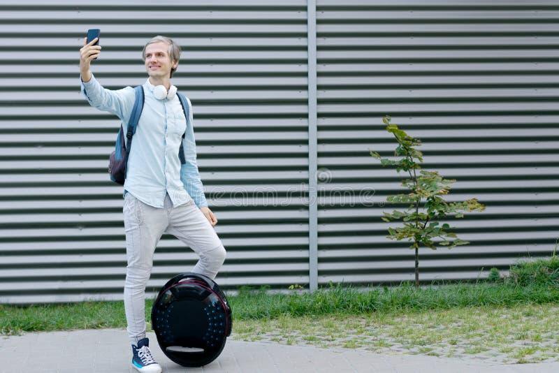 Man för affärsman med elektrisk transport som gör selfie arkivbilder