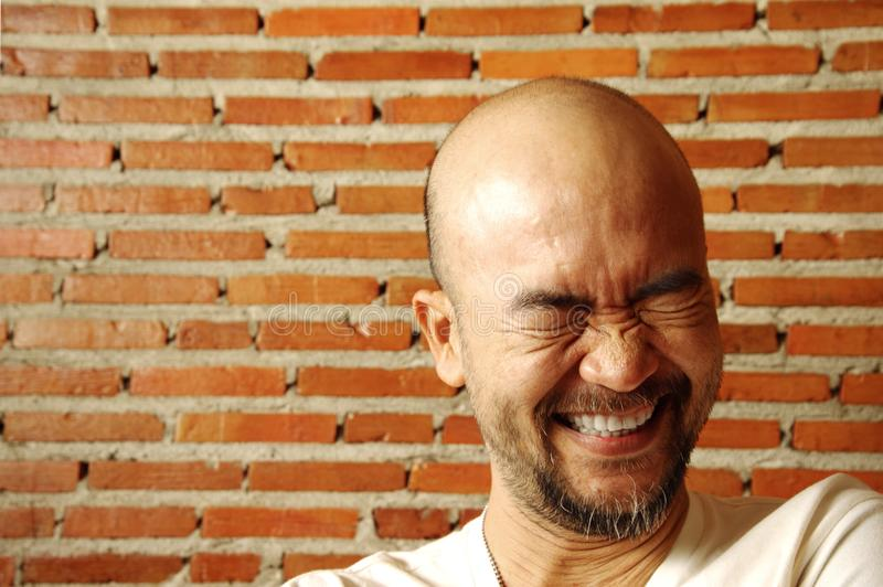 Man för asiatiskt japanskt skägg för stående skallig skratta med tegelstenväggen royaltyfri foto