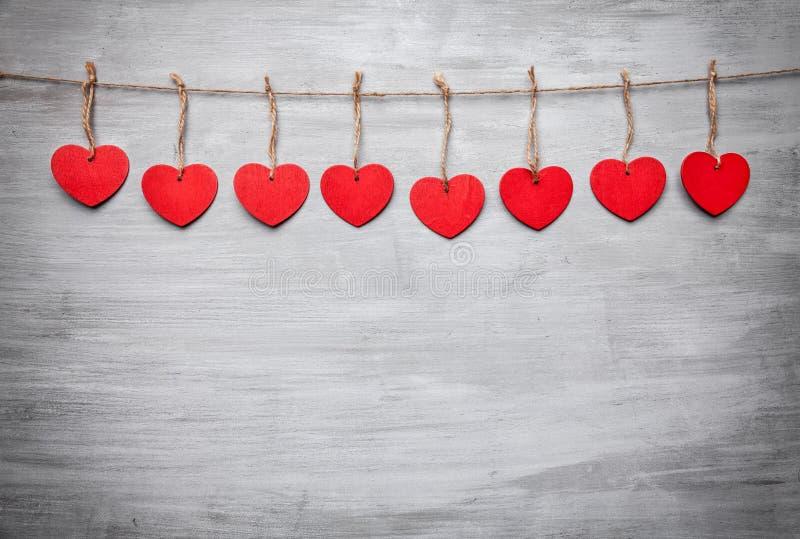 man för begreppskyssförälskelse till kvinnan Hjärtor som hänger på en rad arkivbild