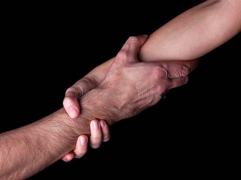 Man för besparing för kvinna för rädda och hjälpa, genom att rymma eller klämma underarmen Kvinnlig hand och arm som drar upp man royaltyfria foton