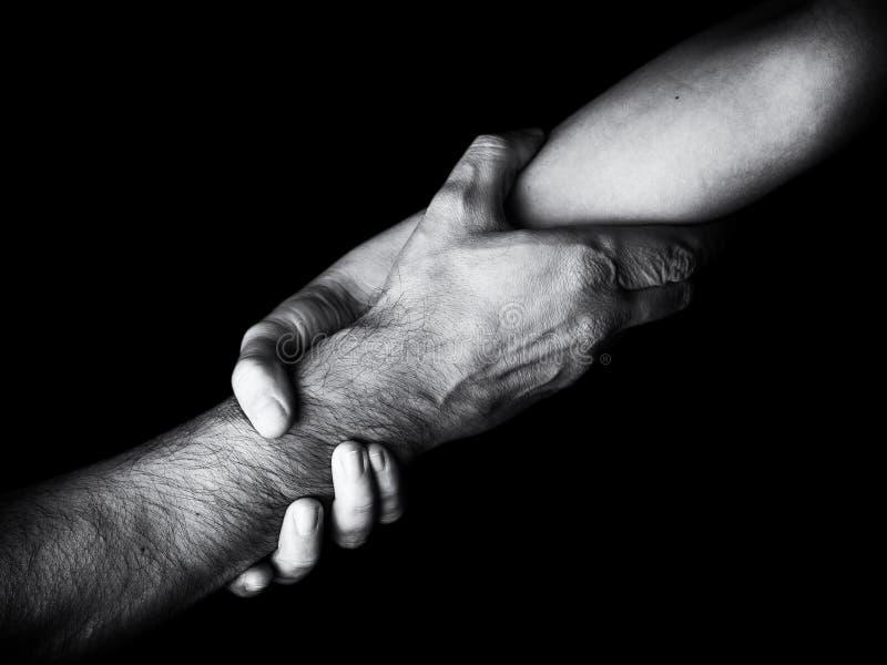 Man för besparing för kvinna för rädda och hjälpa, genom att rymma eller klämma underarmen Kvinnlig hand och arm som drar upp man royaltyfri foto