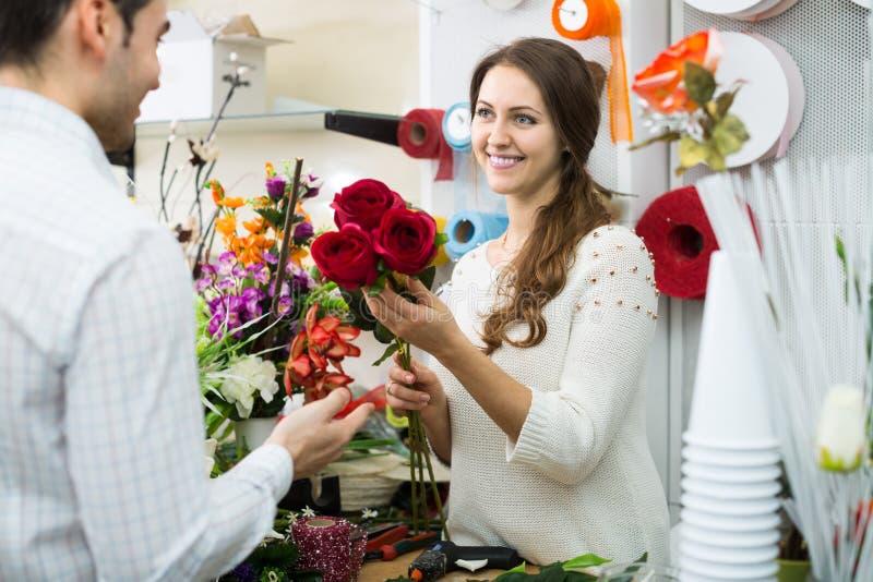 Man för blommor för kvinnasäljare erbjudande fotografering för bildbyråer