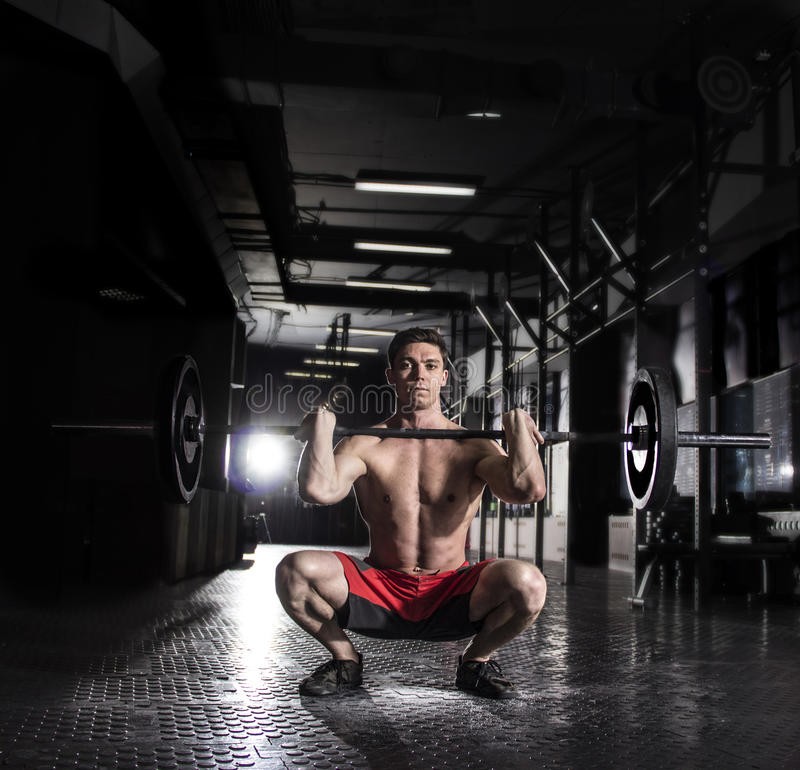 Man för främre satt övning för skivstång idrotts- under intensiv genomkörare arkivfoto