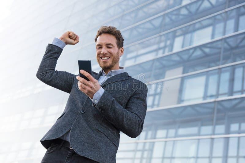 Man för framgångvinnareaffär som segrar på mobiltelefonappen Hurra affärsmannen som ser smartphoneonline-dobbelutmaning eller arb royaltyfri fotografi