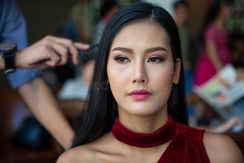 Man för hårstylist som gör frisyren till den unga skönhetmodellen på i kulisserna asiatisk kvinna arkivbild