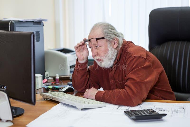Man för hög man som sitter på skrivbordet som bär en skjorta och att ha problem eller problem genom att använda en dator som ser  royaltyfri fotografi