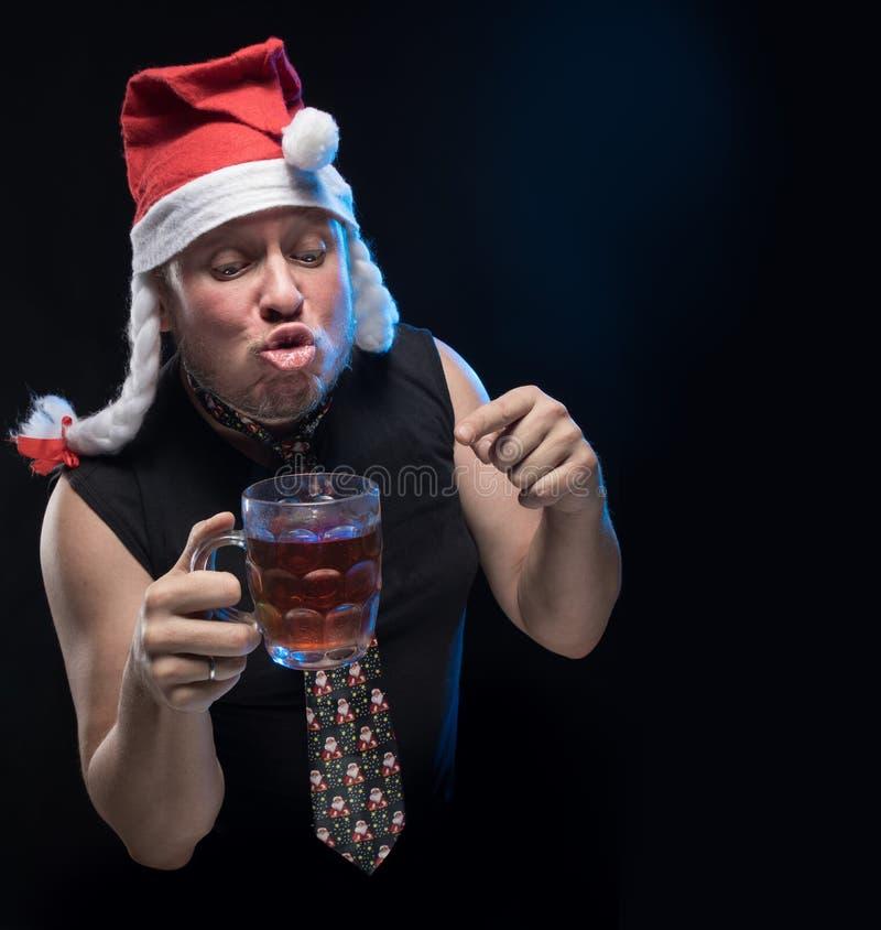 Man för komisk skådespelare i lock med flätade trådar med ett exponeringsglas av öl, i förväntan av jul och det nya året arkivbild