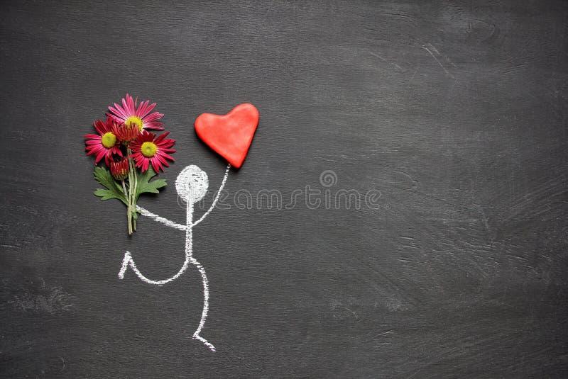 Man för kritateckning med buketten av blommor och stor röd hjärta på svart tavlabakgrund med kopieringsutrymme Valentindaggåva el arkivbilder