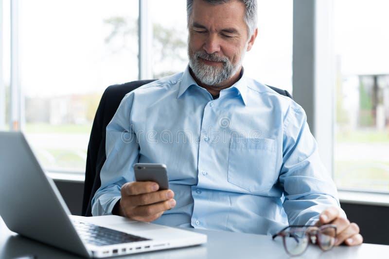 Man för mogen affär i formella kläder genom att använda mobiltelefonen Allvarlig affärsman som använder smartphonen på arbete Che arkivbild