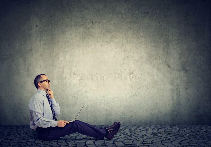 Man för mogen affär med bärbar datorsammanträde på tänka för golv arkivfoton