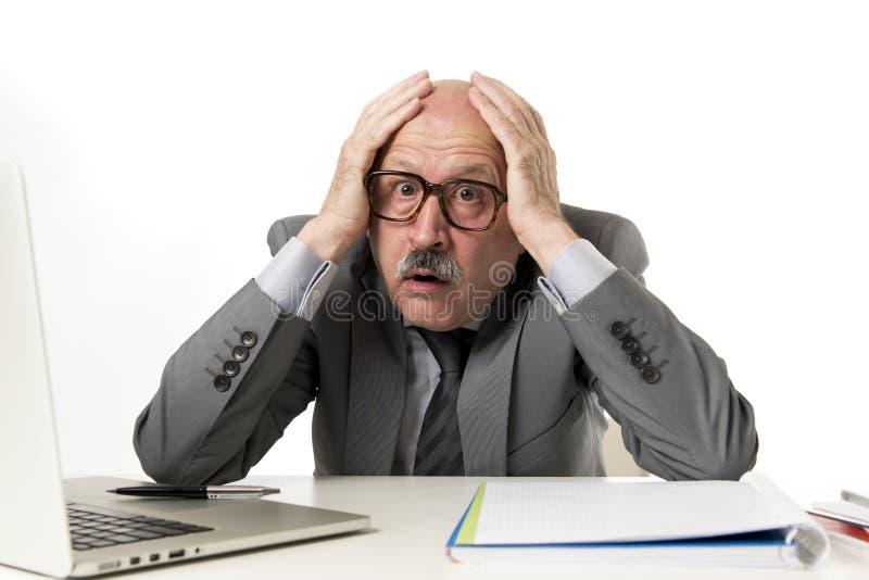 Man för mogen affär med flinten på hans funktionsdugliga stressat för 60-tal och frustrerat på skrivbordet för bärbar dator för k royaltyfria bilder