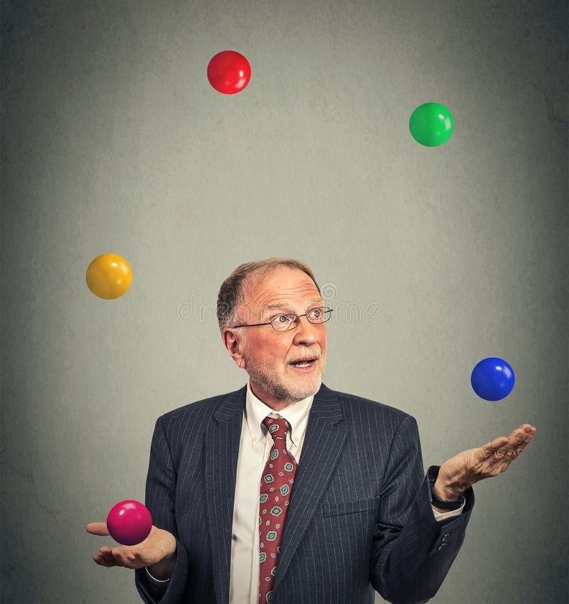 Man för mogen affär som jonglerar multitasking royaltyfri foto