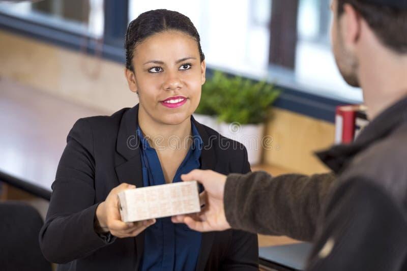 Man för receptionistReceiving Parcel From leverans arkivbilder