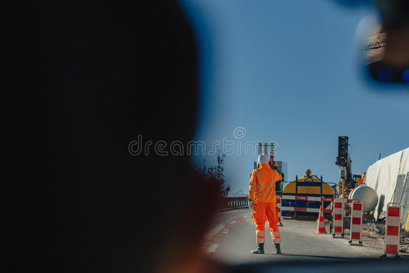Man för serviceväg i orange omslag, Schweiz, alpina berg, solig blå himmel royaltyfri foto