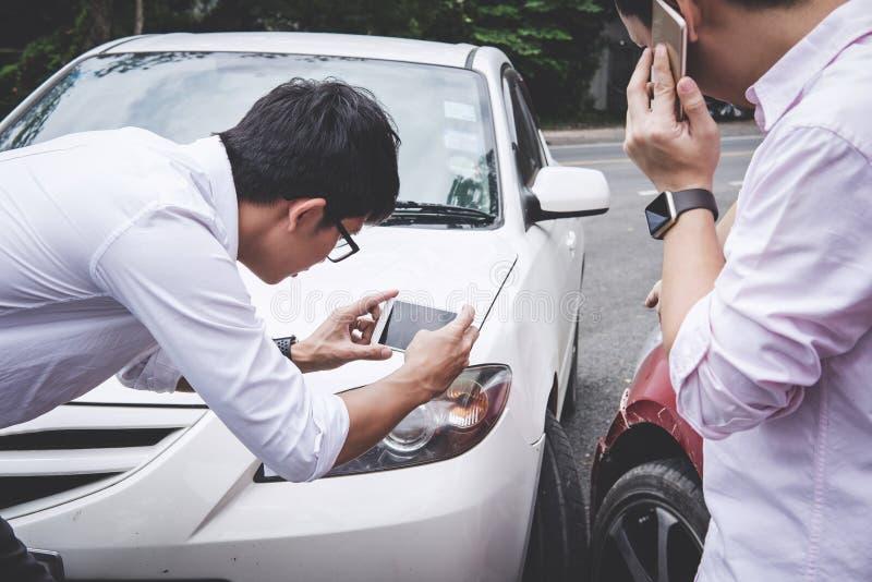Man för två chaufförer som argumenterar efter en biltrafikolyckasammanstötning och gör påringning till försäkringmedlet och att t royaltyfria bilder