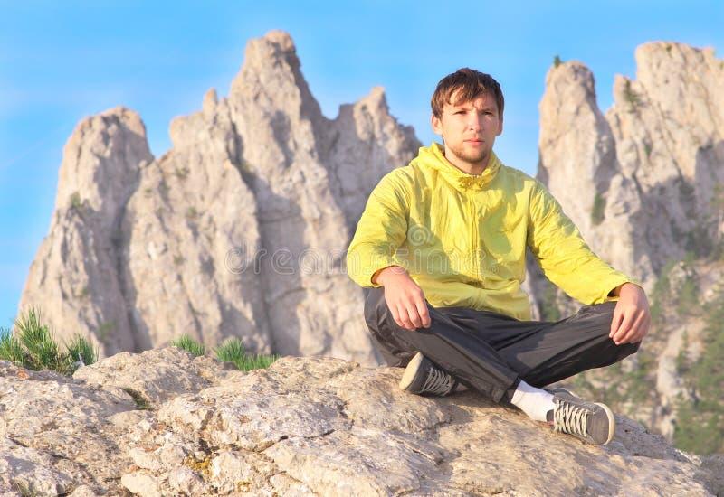 Man för yogameditationen för handelsresanden avslappnande sammanträde på stenar med Rocky Mountains arkivfoton