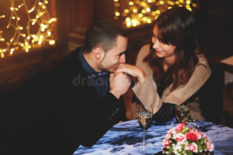 Man försiktigt blickar på flickan och kysser hennes hand royaltyfria bilder