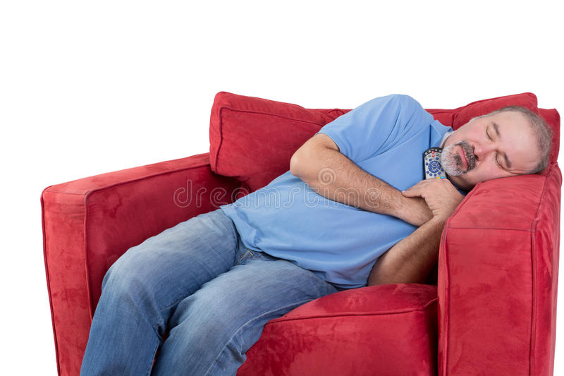 Man fallen asleep while watching television. Tired middle-aged man fallen asleep while watching television with the remote control in his hand and his head royalty free stock image