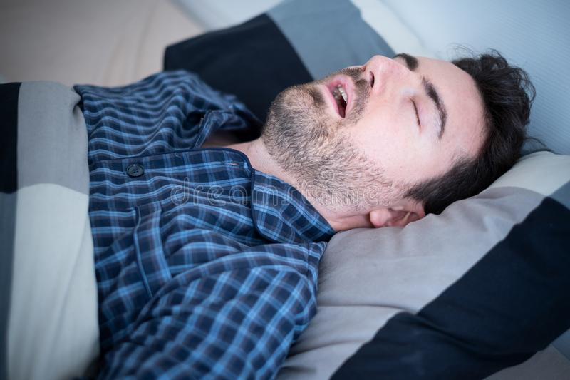 Man falling asleep in his bed at home royalty free stock image