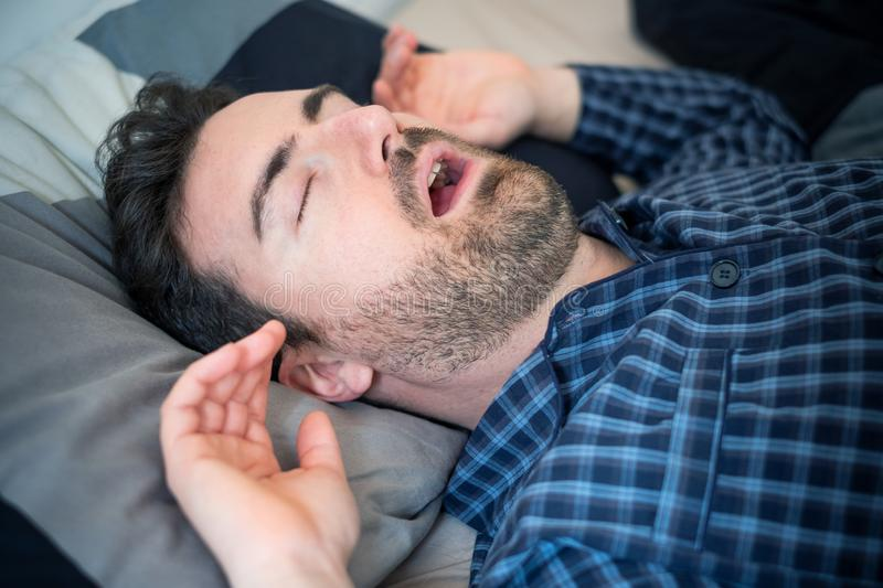Man falling asleep in his bed at home royalty free stock photo