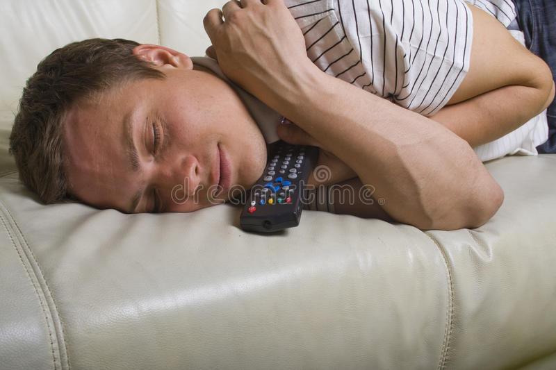 Man falling asleep with TV remote control. On white leather sofa royalty free stock photos