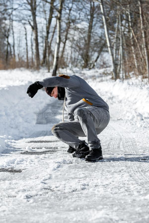 Man falling becauce of black ice on the road, danger on winter season. Caucasian man falling becauce of black ice on the road, danger on winter season stock images