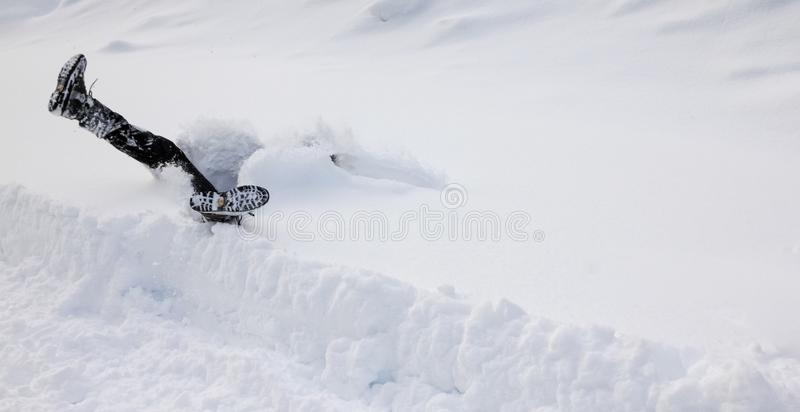 Man is falling headfirst into deep snow. Concept of winterly slippery conditions. Man is falling headfirst and legs up in the air into deep snow. Winterly royalty free stock photography