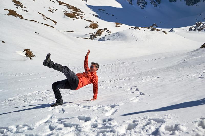 Man falling on its back on snow, with a funny body position, at Malaiesti Valley, Bucegi mountains, Romania, on a sunny Winter day stock photos