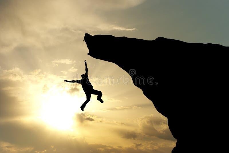 Man falling from the mountain. Edge. Conceptual scene stock photos