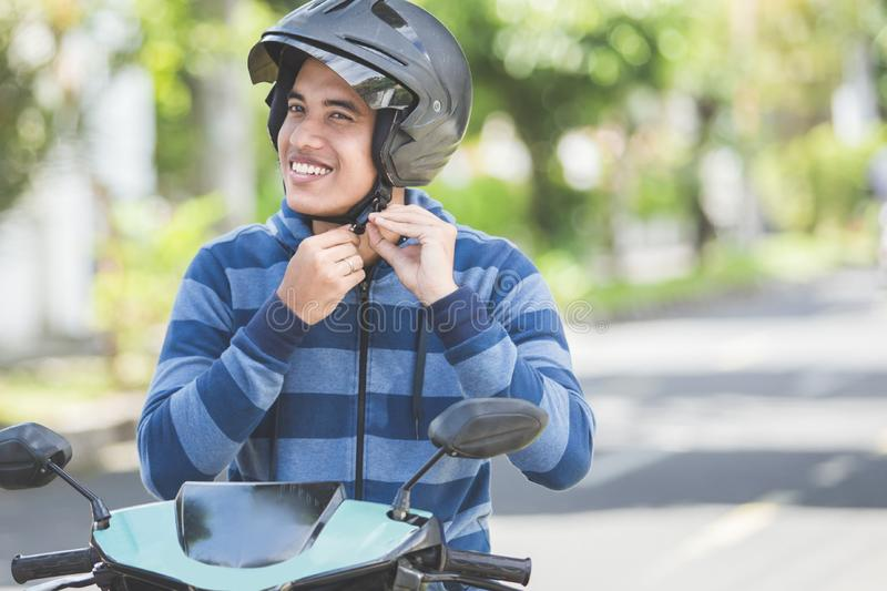 Man fastening his motorbike helmet royalty free stock images