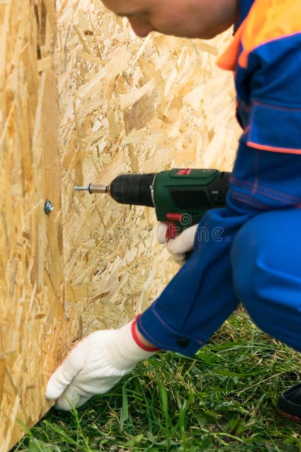 The man fastens a large sheet of board with an electric screwdriver, close-up. The man fastens a large sheet of  board with an electric screwdriver, close-up stock image
