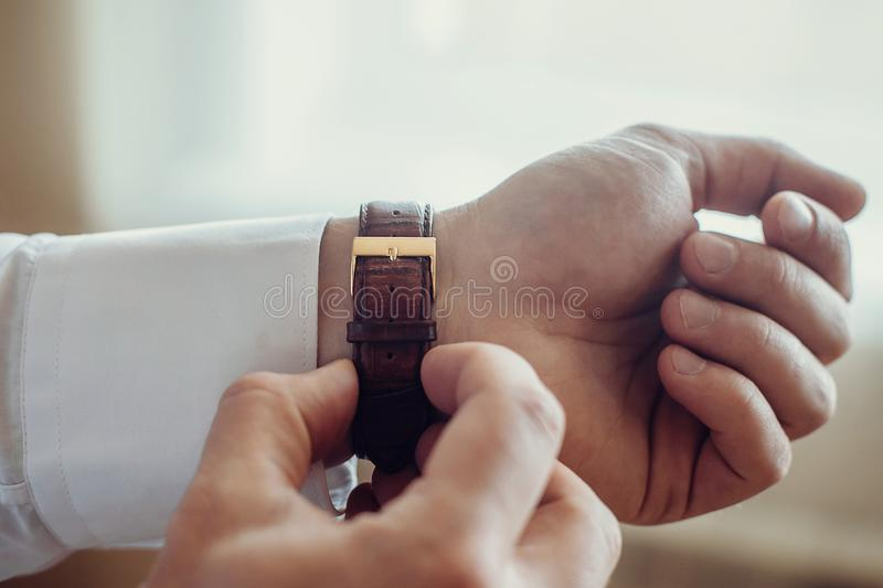 A man fastens a wrist watch on his hand close-up.  stock photography