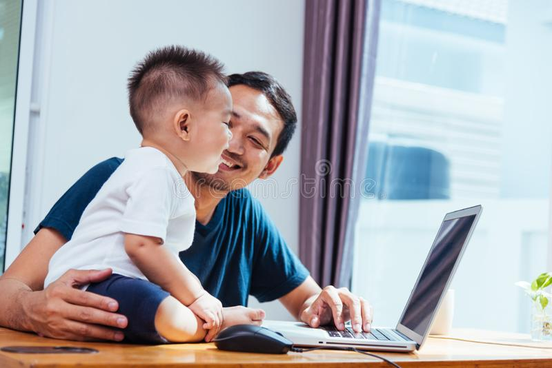 Man father working on laptop computer stock images