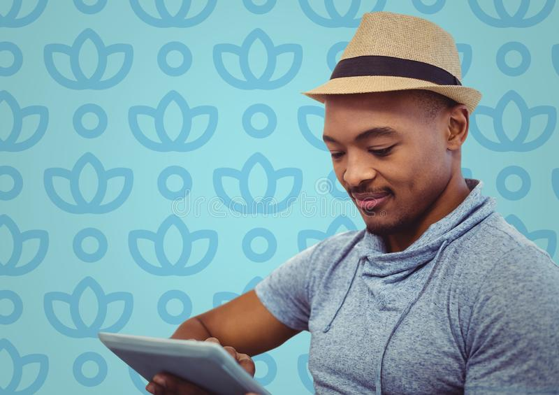 Man in fedora with tablet against blue floral pattern. Digital composite of Man in fedora with tablet against blue floral pattern stock photos
