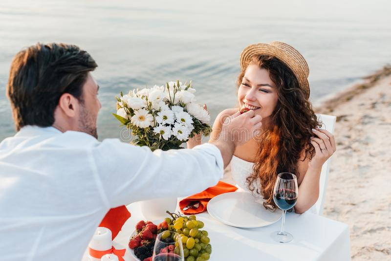 man feeding smiling girl with strawberry during romantic date stock photos