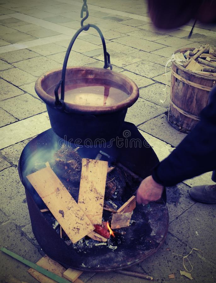 Man feeds the fire lit to boil the water inside the copper pot d. Man feeds the fire lit to boil the water inside the old copper pot during reenactment medieval royalty free stock image