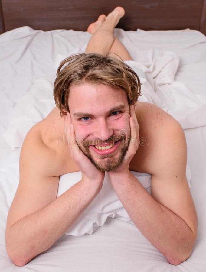 Man feel full of energy after pleasant night dream. Playful mood concept. Guy macho lay white bedclothes. Pleasant. Relax concept. Man unshaven handsome happy stock photo