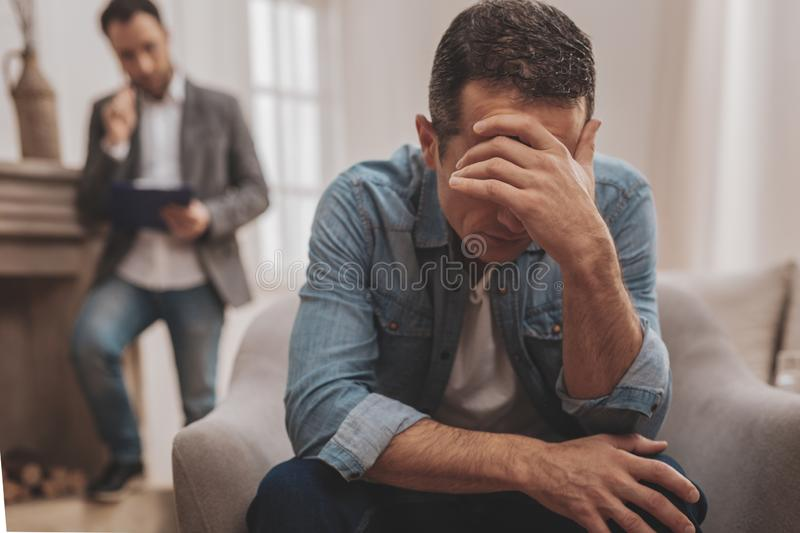 Man feeling awful telling about interpersonal problems. Interpersonal problems. Stressed emotional men feeling rather awful while telling about his interpersonal royalty free stock image
