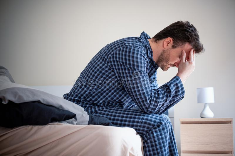 Man feeling bad and seated on the bed. Depressed man portrait sitting on the bed royalty free stock images