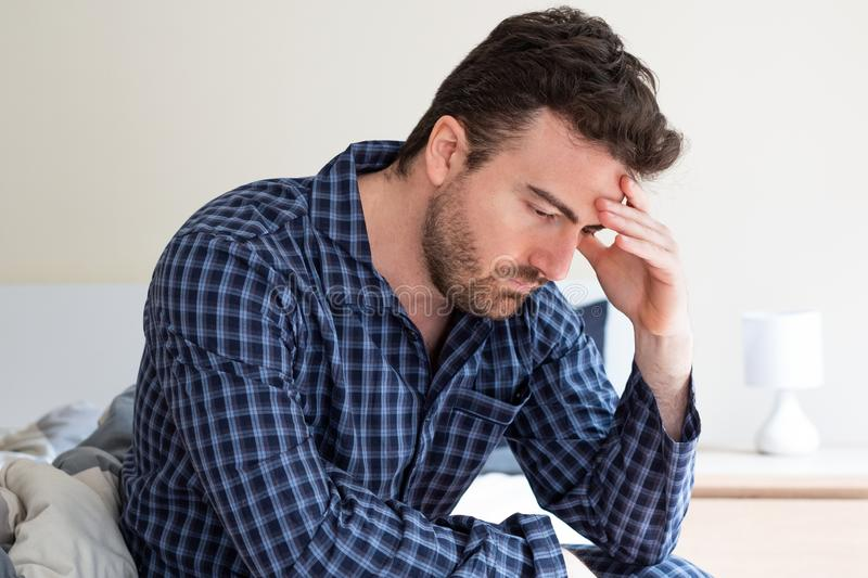 Depressed man portrait sitting on the bed. Man feeling bad and seated on the bed stock photos