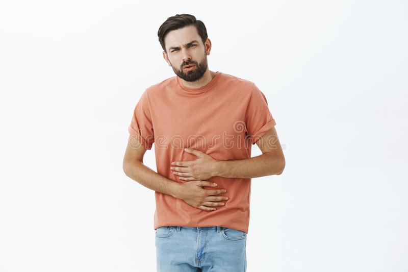 Man feeling discomfort in stomach eating fast food, holding hands on belly exhaling hard and grimacing from pain, having stock photo
