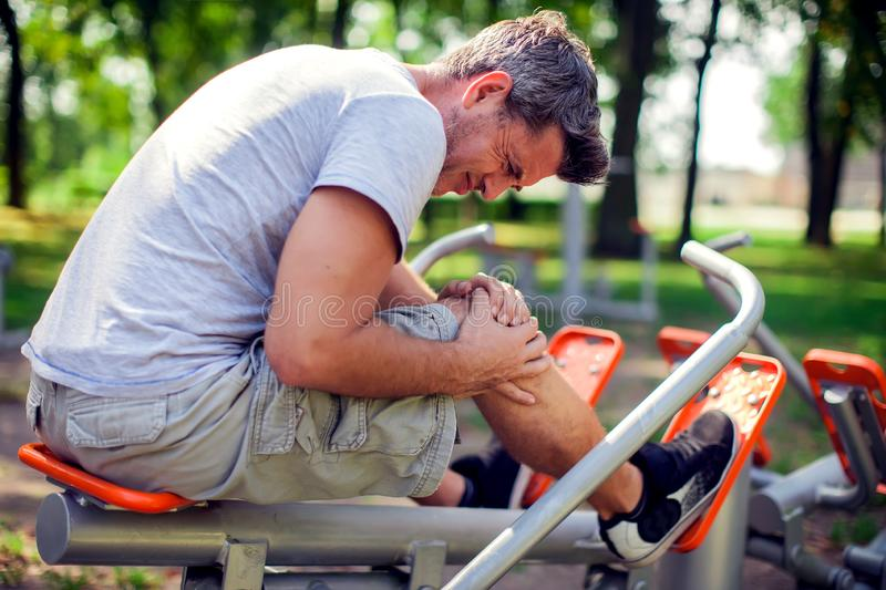 A man feeling pain in his knee during sport and workout in the p. An unhappy man feeling pain in his knee during sport and workout in the park. Sport, medicine stock images