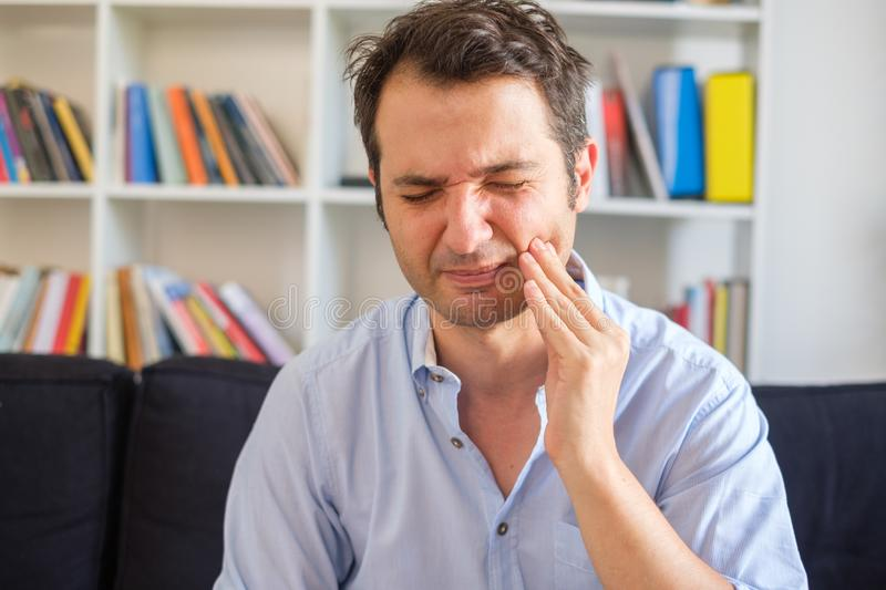 Man with gum disease feeling pain and sick. Man feeling toothache because of periodontitis royalty free stock photos