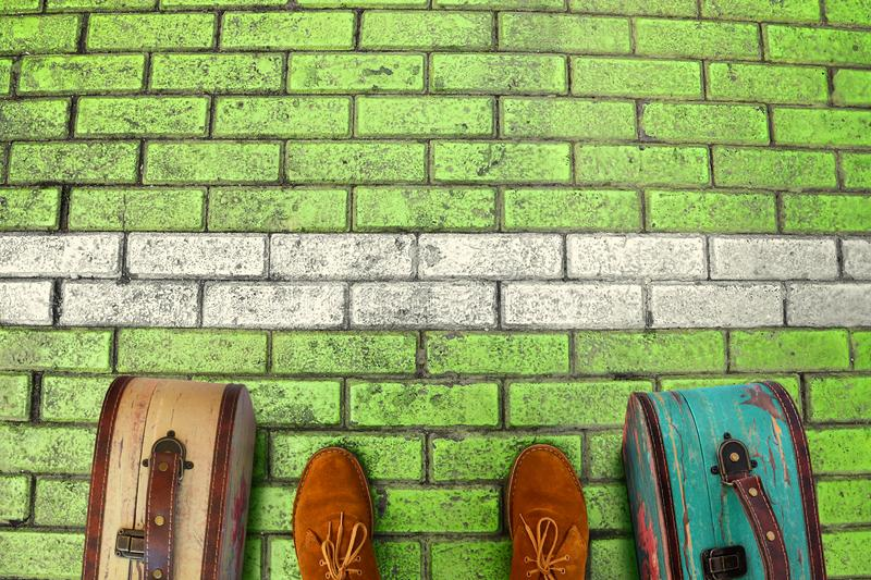 Man feet in suede boots. Vintage suitcases stand on paving stone green road. Person stands in front of a white boundary l stock image