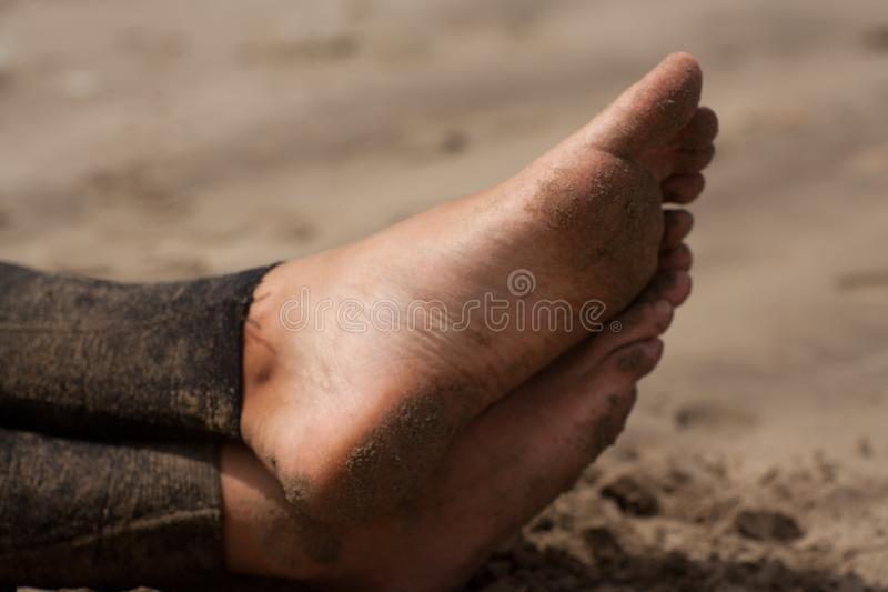Man feet, surfer with wetsuite sitting on the beach waiting for the waves stock image