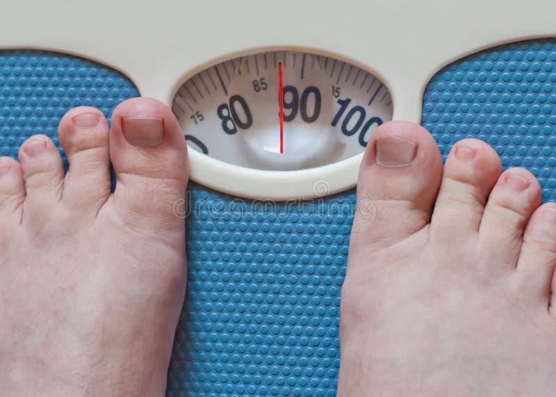Man feet weighing in bathroom stock photo