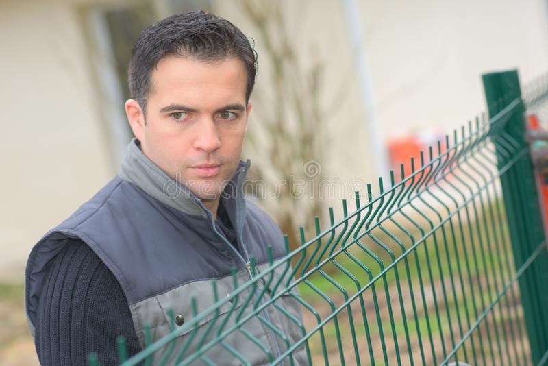 Man at a fence. Work royalty free stock images