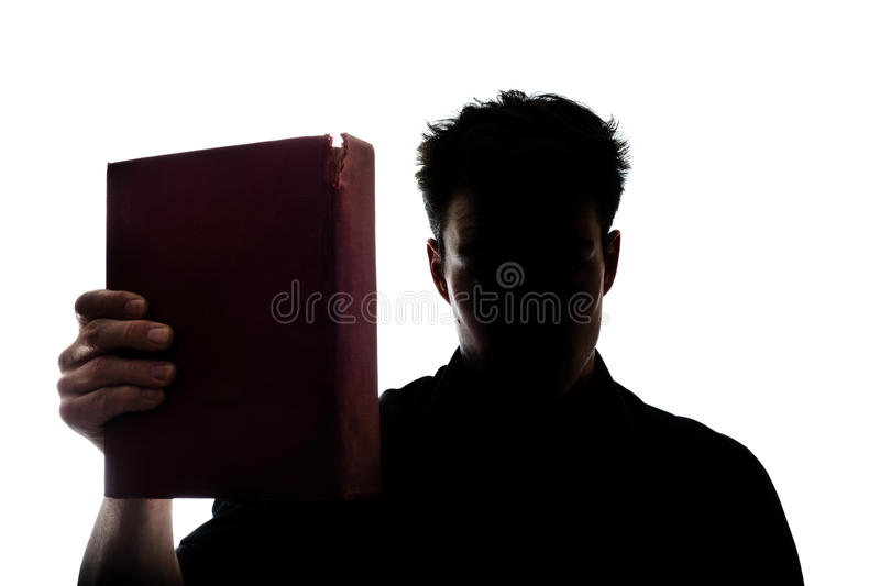 Man figure in silhouette showing a book royalty free stock photography
